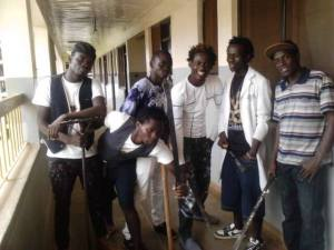 Tripple S poses for a photo with a group of youths after engaging in community work