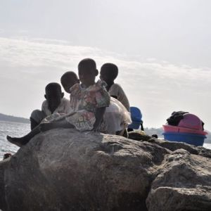 Kids resting on a rock on the shores of Lake Victoria. #TembeaKenya.