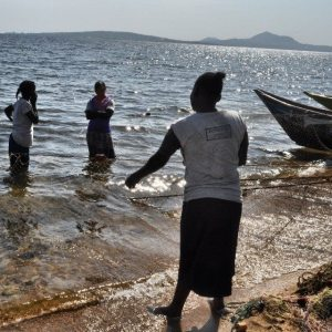 A woman pulling a fishing net in Lake Victoria. #TembeaKenya.