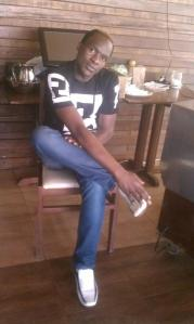 Sweet Boy poses for a photo at his work place, Nova Cafe located at Zion Mall in Eldoret town.